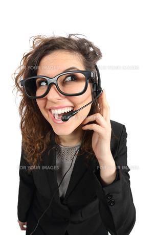 Happy geek telephone operator woman attending a callの写真素材 [FYI00634875]