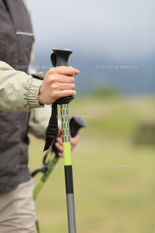 Close up of a hiker hands holding a hiking pole while walkingの素材 [FYI00634881]