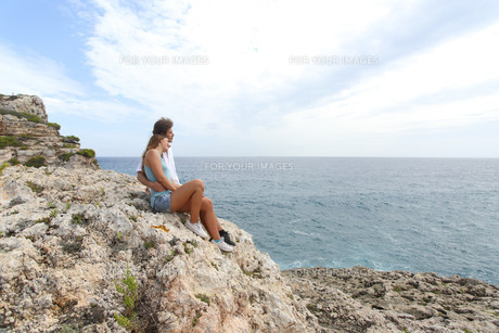 Teenager couple looking at horizon on a cliffの写真素材 [FYI00634886]