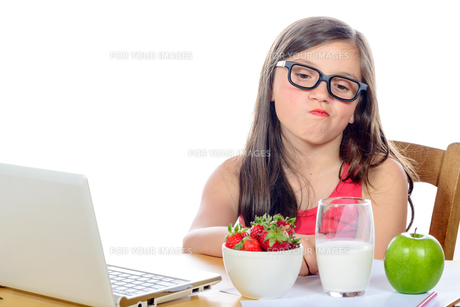 a little girl at her desk looking at his snackの写真素材 [FYI00635386]