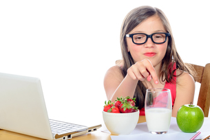 a little girl at her desk looking at his snackの写真素材 [FYI00635391]