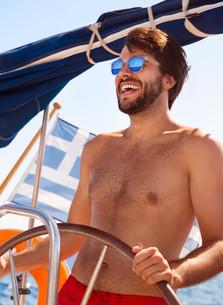 Happy guy behind wheel of sailboatの素材 [FYI00635565]