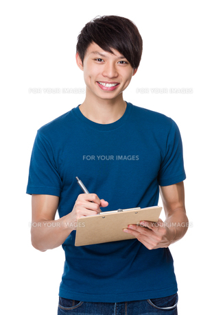 Asian man write on clipboardの写真素材 [FYI00635853]