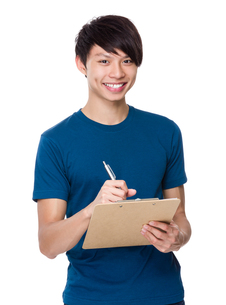 Young man write on clipboardの写真素材 [FYI00635858]