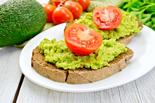 Sandwich with guacamole avocado and tomato on light boardの写真素材 [FYI00636094]