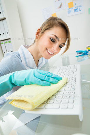 Maid Cleaning Keyboard At Deskの写真素材 [FYI00636741]