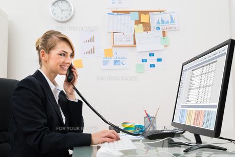 Businesswoman Talking On Telephone At Deskの写真素材 [FYI00636792]