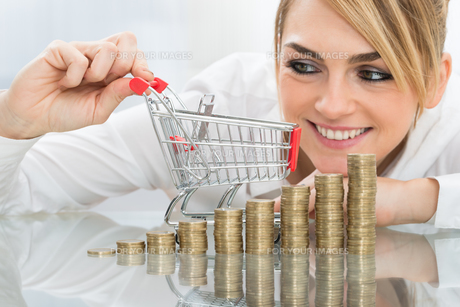 Businesswoman With Mini Shopping Cart And Coinsの写真素材 [FYI00636835]