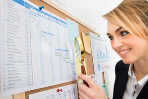 Businesswoman Examining Gantt Chart With Magnifying Glassの写真素材 [FYI00637120]
