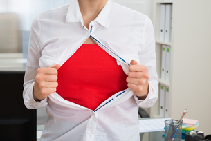 Businesswoman Tearing Her Shirt Showing Red Costumeの写真素材 [FYI00637136]
