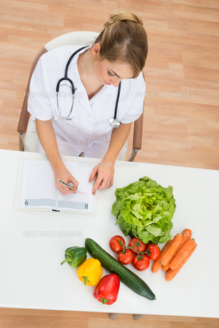 Female Dietician Writing In Diaryの写真素材 [FYI00637169]