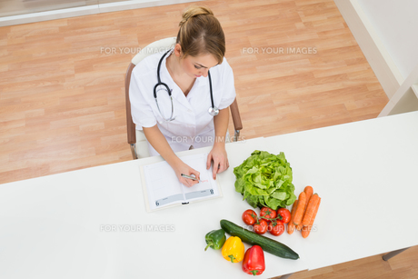 Female Dietician Writing In Diaryの写真素材 [FYI00637171]