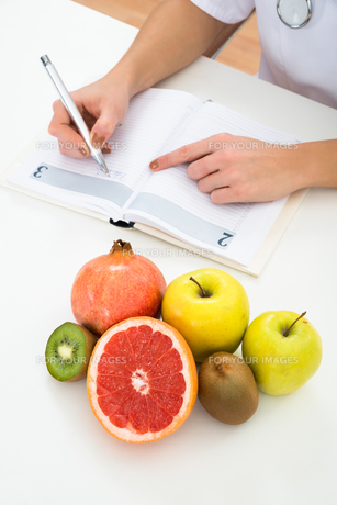 Dietician Writing Prescription With Fruits On Deskの写真素材 [FYI00637184]