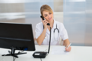 Young Female Doctor Talking On Telephoneの写真素材 [FYI00637190]