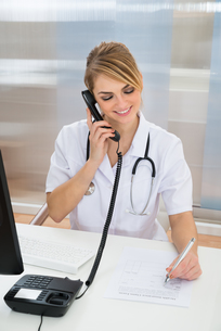 Young Female Doctor Talking On Telephoneの写真素材 [FYI00637196]