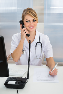 Young Female Doctor Talking On Telephoneの写真素材 [FYI00637197]