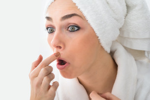 Shocked Woman Looking At Pimple On Faceの素材 [FYI00637214]