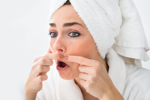 Shocked Woman Looking At Pimple On Faceの素材 [FYI00637217]