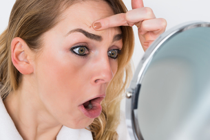 Woman Looking At Pimple In Mirrorの素材 [FYI00637248]