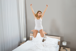 Excited Woman Jumping On Bedの写真素材 [FYI00637272]