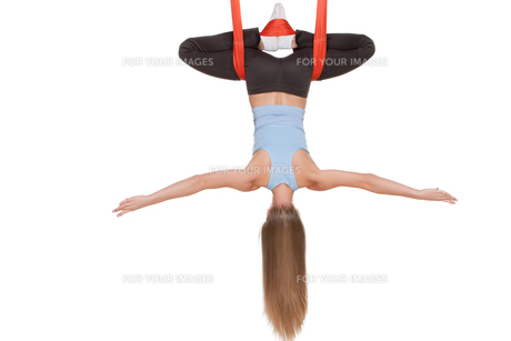 Young woman doing anti-gravity aerial yoga in hammock on a seamless white background.の写真素材 [FYI00637289]
