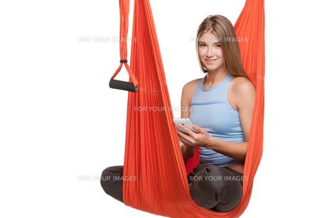Young woman sitting in hammock for anti-gravity aerial yogaの写真素材 [FYI00637294]