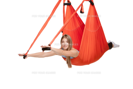 Young woman doing anti-gravity aerial yoga in hammock on a seamless white background.の写真素材 [FYI00637295]