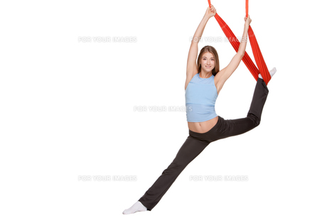 Young woman making antigravity yoga exercises in stretching twineの写真素材 [FYI00637298]