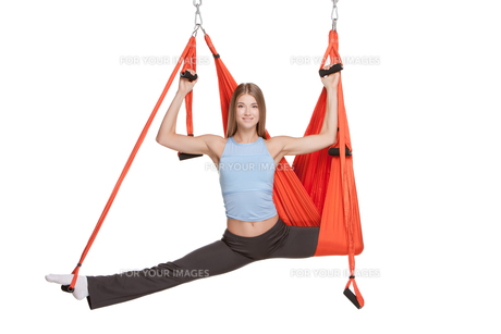 Young woman making antigravity yoga exercises in stretching twineの写真素材 [FYI00637306]