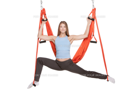 Young woman doing anti-gravity aerial yoga in hammock on a seamless white background.の写真素材 [FYI00637307]