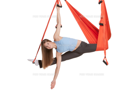 Young woman doing anti-gravity aerial yoga in hammock on a seamless white background.の写真素材 [FYI00637308]