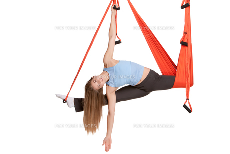 Young woman doing anti-gravity aerial yoga in hammock on a seamless white background.の素材 [FYI00637309]