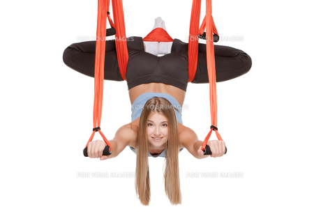 Young woman making antigravity yoga exercises in stretching twineの写真素材 [FYI00637311]