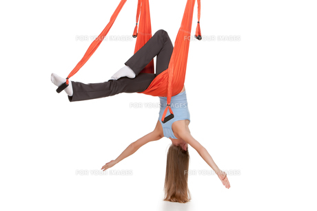 Young woman doing anti-gravity aerial yoga in hammock on a seamless white background.の写真素材 [FYI00637312]