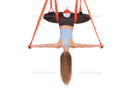 Young woman doing anti-gravity aerial yoga in hammock on a seamless white background.の写真素材 [FYI00637314]