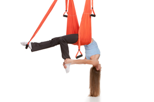 Young woman doing anti-gravity aerial yoga in hammock on a seamless white background.の素材 [FYI00637316]