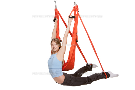 Young woman doing anti-gravity aerial yoga in  red hammock on a seamless white background.の写真素材 [FYI00637322]