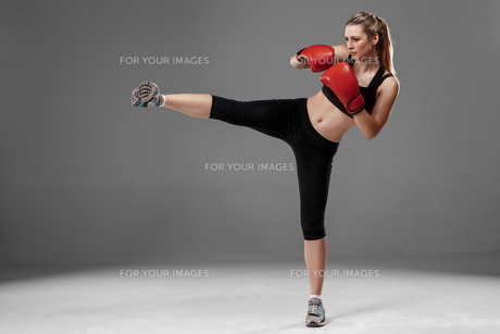 beautiful woman is boxing on gray backgroundの写真素材 [FYI00637360]