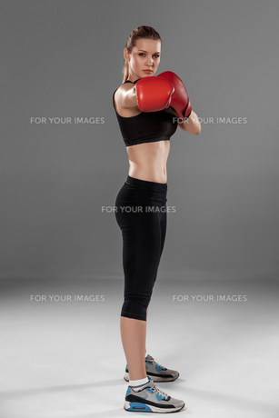 beautiful woman is boxing on gray backgroundの写真素材 [FYI00637361]