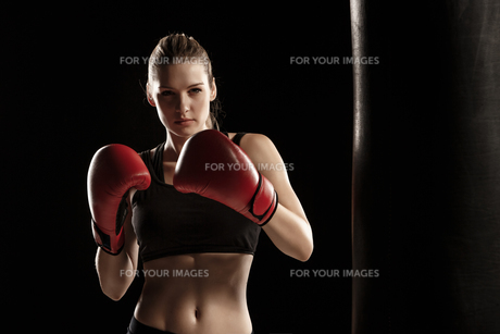 beautiful woman is boxing on black backgroundの写真素材 [FYI00637368]