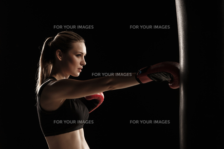beautiful woman is boxing on black backgroundの写真素材 [FYI00637371]