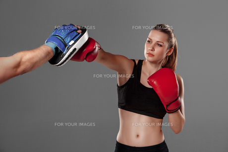 beautiful woman is boxing on gray backgroundの写真素材 [FYI00637379]