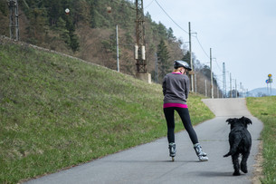 Woman is skating on rollerblades beside her dog outdoors.の写真素材 [FYI00637429]