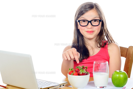 a little girl at her desk looking at his snackの写真素材 [FYI00637777]