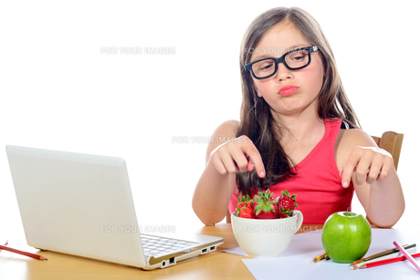 a little girl at her desk looking at his snackの写真素材 [FYI00637930]