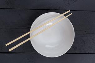 bowl with chopsticks on a black wooden bird's eye viewの写真素材 [FYI00637992]