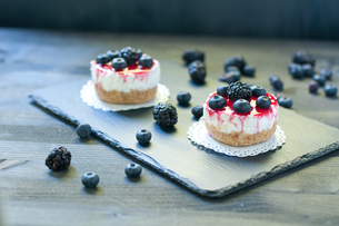delicious strawberry cheese cake on a black plate with fresh blueberries in the backgroundの写真素材 [FYI00638230]