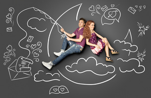 Happy valentines love story concept of a romantic couple fishing on a moon with a paper letter on a hook against chalk drawings background.の写真素材 [FYI00639712]