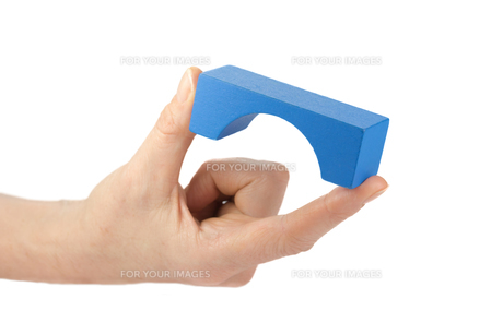 Blue wooden toy bridge in female fingers isolatedの写真素材 [FYI00639932]