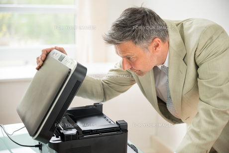 Businessman Looking At Photocopy Machineの写真素材 [FYI00640376]